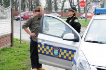 Strażnicy przepytują mężczyznę podejrzewanego o nielegalny wywóz śmieci.